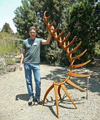 Artist David Mudgett with his sculpture Tune A Fish, in steel.