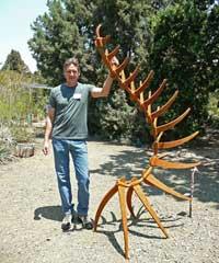 Artist David Mudgett with his sculpture Tune A Fish, in steel.